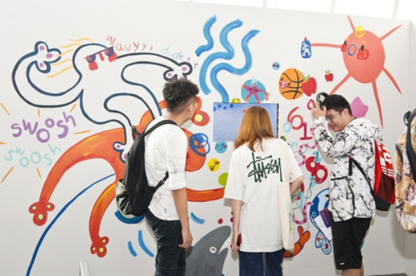 Students engaging with a video at a degree show